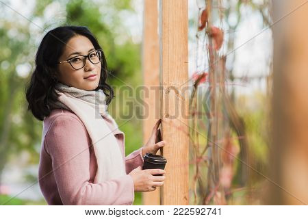 Beautiful young asian woman posing with cup of hot drink outdoor. A girl with glasses looks at the camera.