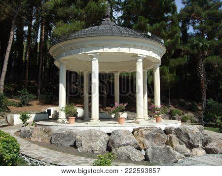 Partenit, Crimea, Russia - JULY 15, 2012: White Greek round Stone Gazebo veranda in Aivazovsky park. Partenit park. Suuny day. Crimea. Russia
