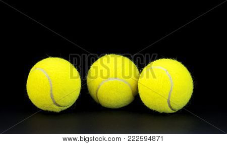 Yellow felt tennis balls on black background. Tennis ball photo for banner template. Sport equipment isolated. Tennis competition backdrop. Yellow felt ball for active game. Summer sport activity