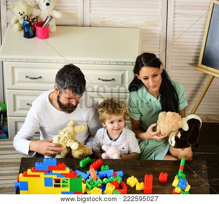 Parents and son with smiling faces make brick constructions. Mom, dad and boy play with toys on wooden background. Young family spends time in playroom. Love and family games concept