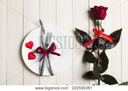 Valentines day table setting romantic dinner marry me wedding engagement with red rose gift and plate fork knife on white wooden background with copyspace. Love flower gift woman making proposal