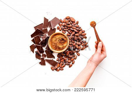 Make chocolate. Cocoa powder in bowl near cocoa beans and pieces of chocolate on white background top view.
