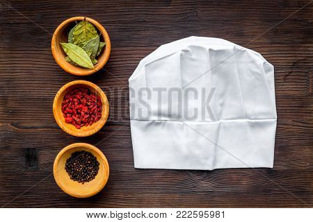 Make menu or write recipe. Mock up for menu or recipe. Chief hat near ingredients in bowls bay leaf, black repper and godji on dark wooden background top view.