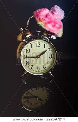 White retro clock with a winter hat isolated against a dark background casting a reflection