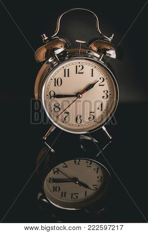 White retro clock isolated against a dark background casting a reflection