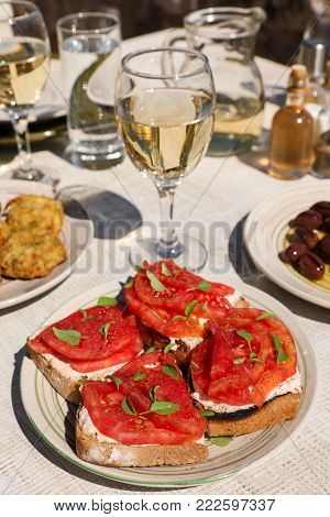 Sandwiches with feta cheese, fresh tomatoes, basil leaves as an appertizer next to plates of zucchini balls, olive olives and white wine, water glasses served in greek tavern. Vertical. Close-up.