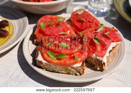 Sandwiches with feta cheese, fresh tomatoes, basil leaves as an appertizer in greek tavern. Horizontal. Daylight. Close-up.