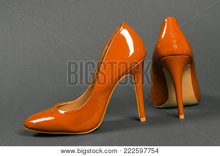 Lacquered orange high heels shoes on gray background.