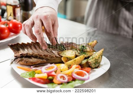 the chef prepares in the restaurant. Grilled rack of lamb with fried potatoes and fresh vegetables.