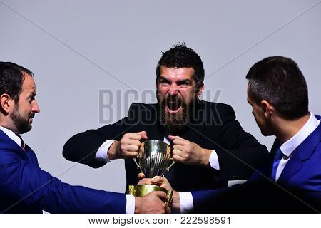 Coworkers or partners fight for winning competition. Company leaders hold golden prize. Business conflict and argument concept. Businessmen with mad faces in formal suits on grey background