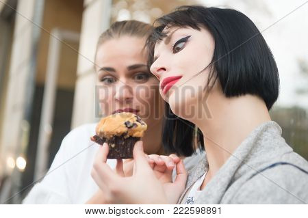 Women look at cupcake in paris, france. Girl friends with blueberry muffin in cafe. Hunger, temptation, appetite concept. Dessert, food, snack, pastry. poster