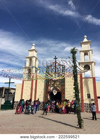 EL CONEJO, PEROTE, VERACRUZ, MEXICO- DECEMBER 16, 2017: People outside of a colorful church decorated with a floral arch at a wedding  in a sunny day at El Conejo, town near to Perote, Veracruz, Mexico