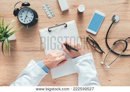 Overhead view of male doctor writing notes, patient's medical history or medicine prescription on clipboard paper during medical exam in hospital office