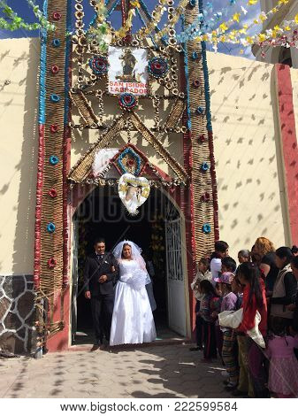 EL CONEJO, PEROTE, VERACRUZ, MEXICO- DECEMBER 16, 2017: Couple of newly weds leaving of a colorful church decorated with a floral arch in a sunny day at El Conejo, town near to Perote, veracruz, Mexico