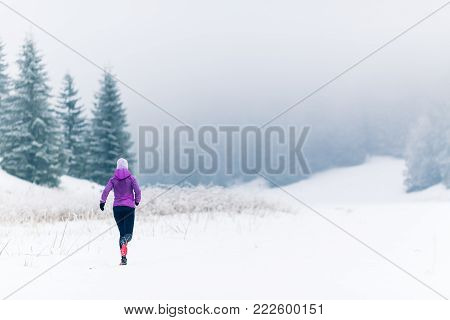 Woman trail running in mountains on snow footpath, winter day. Sport, fitness inspiration and motivation. Girl cross country runner training in cold conditions.