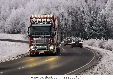 SALO, FINLAND - JANUARY 12, 2018: Customized Volvo FH16 750 logging truck of R.M. Enberg Transport Ab hauls a log load along rural highway through frosted winter landscape in the evening.
