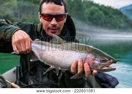 Fisherman holding the catch of Rainbow trout (Oncorhynchus mykiss) on bellyboat, Jesenice, Slovenia. Fly fishing and outdoor lifestyle theme.