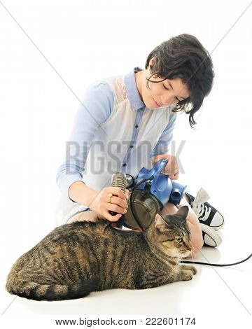 An attractive young teen vacuuming her relaxed pet cat with a portable vacuum cleaner, making the hair on his back stand up.  On a white background.