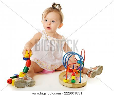 A beautiful baby girl playing with a big, colorful beads on a string and wire frame.  On a white background.