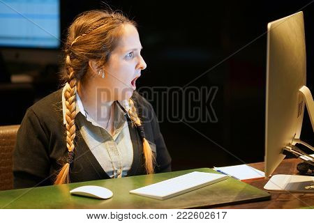 Hotel manager. A blonde woman-reception shocked sitting in front of the monitor of computer. Funny face expression emotion feelings problem perception reaction, stress, fear