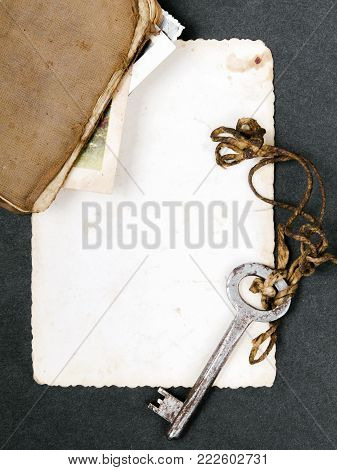 Rusty key, old book and empty photography as a memories  metaphor. Copy space