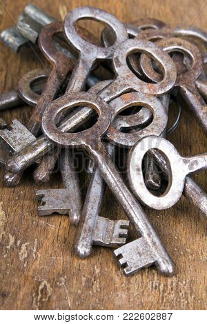 Old rusty keys on wooden background, top cview