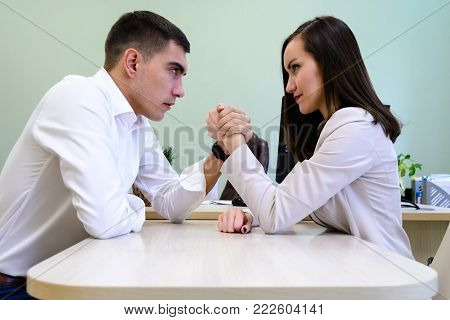 Man and woman in office clothes struggling on his hands over the Desk in the office.