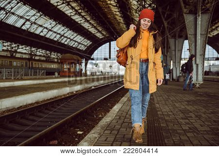 young woman walk by railway station in cold weather