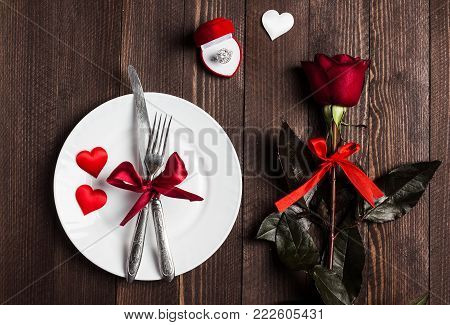 Valentines day table setting romantic dinner marry me wedding engagement ring in box with red rose gift and plate fork knife on dark wooden background with copyspace. Love flower gift making proposal