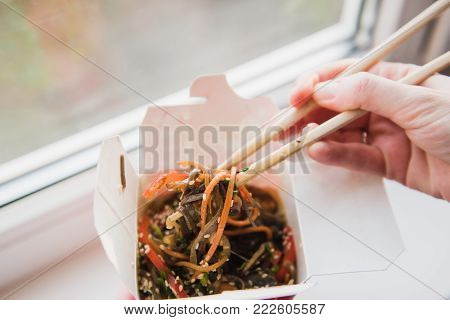 Take-out boxes and chopsticks. Hands with chopsticks taking food out of the box with Asian food. Noodles with vegetables in take-out box. Window in the background.