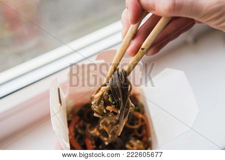 Hands with chopsticks taking food out of the box with Asian food. Noodles with vegetables in take-out box. Window in the background.