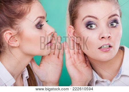 Young woman telling her friend some secrets, two women talking gossiping. Excited emotional girl whispering to human ear