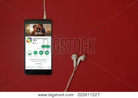 Los Angeles, January 11, 2018: Smartphone with Disco gay dating and gay chat application in google play store on red background with earphones plugged in and copy space