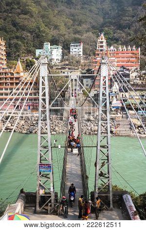 RISHIKESH, INDIA - February, 12th, 2012. Beautiful view of Ganga river embankment, Lakshman Jhula bridge and Tera Manzil Temple, Trimbakeshwar in Rishikesh