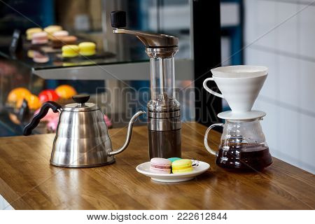 On a wooden table in the cafe are items for making coffee. On the table are tea pots and a coffee pot against the backdrop of bright cakes.