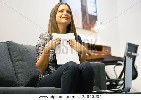 Happy woamn enjoying good news in written notice. Euphoric girl happy after reading good news in written letter, loan approvale.