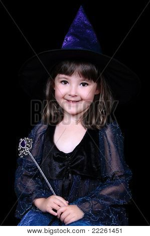 Adorable little Girl In Witch Costume Holding Wand. Isolated