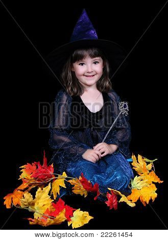 Fun Little Witch Surrounded By Golden Fall Leaves. Isolated