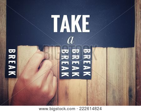 Motivational and inspirational quotes words - 'Take a break' written on a black paper with background of wooden wall. A hand is pulling off one of the 'break' word.