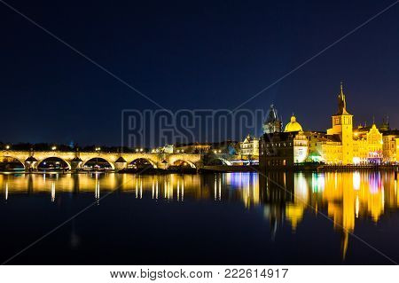 Beautifull night view of the Charles Bridge, the Old Town Bridge Tower, and the Old Water Tower, the Smetana Embankment and the Prague Beer Museum in Czech Republic New Year's Eve.