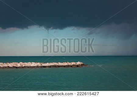 The storm on the sea begins. Dark blue clouds with rain. Before the start of a tornado. The calm sea is azure before the hurricane.