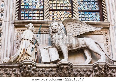Winged Lion and a priest. Detail of the Doge's Palace Palazzo Ducale in Venice, Italy