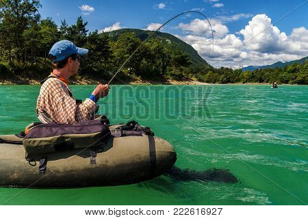 Fisherman sitting in bellyboat and fighting with big trout on lake in Jesenice, Slovenia. Still water fly fishing and outdoor lifestyle theme.