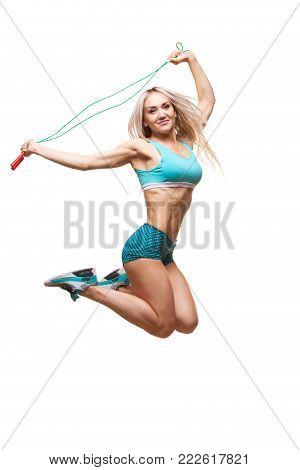 Full length image of a young sports woman jumping on skipping rope over white background.