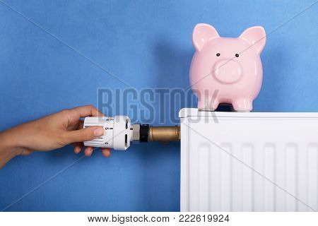 Person Hand Adjusting Temperature On Thermostat To Save Money On Energy Bill