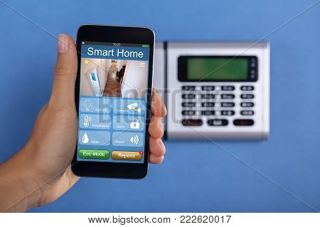 A Person Holding Mobile Phone With Home Security Application In Front Of Security System