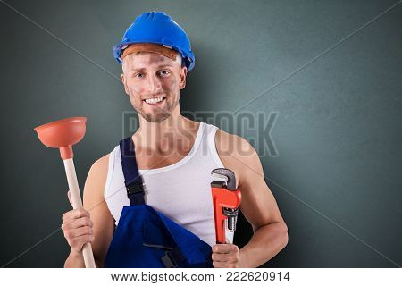 Portrait Of A Happy Plumber Holding Wrench And Plunger On Grey Background