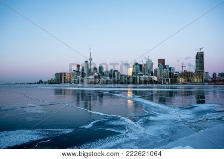 The skyline of Toronto looking across a frozen Lake Ontario in the depths of a cold winter.
