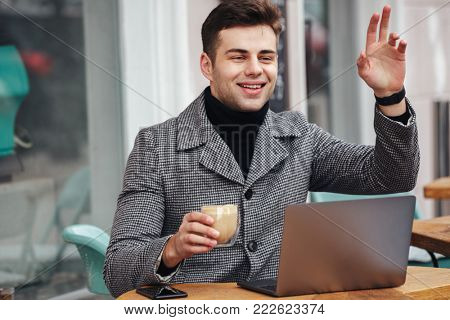 Portrait of joyous young guy smiling and waving hand having appo