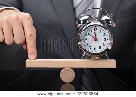 Close-up Of A Person's Finger Balancing Alarm Clock On Wooden Seesaw